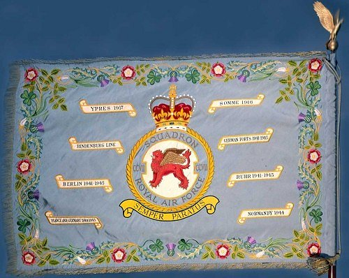 Please click this image for HM The Queen's presentation speech: the Standard, a fringed and tasselled silken banner, mounted on a pike surmounted by a Golden Eagle, was created by His late Majesty King George VI to mark the twenty fifth anniversary of the Royal Air Force in 1943. Squadrons qualify for the award of a Standard after twenty five years of service or for especially meritorious operations. Eight selected battle honours in scroll surround the Squadron badge. The decorative border is embroidered with the national emblems of the British Isles.  [image: Barry Goodwin]